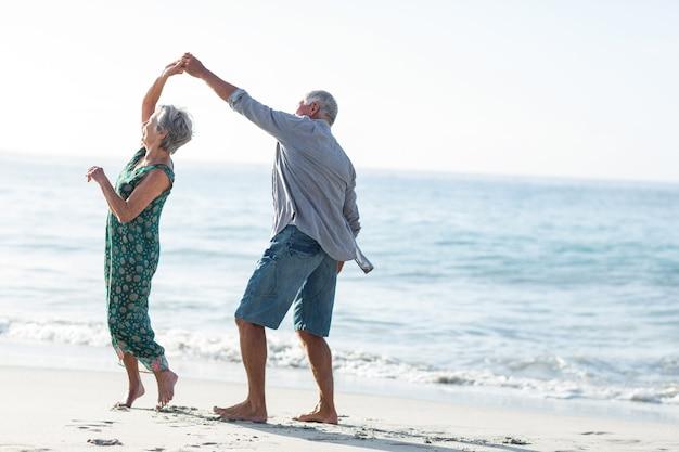 Pareja mayor, bailando, en la playa
