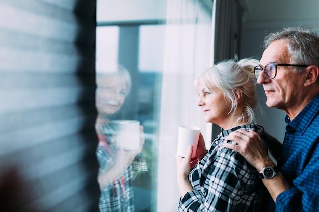 Pareja mayor en casa de ancianos mirando por ventana