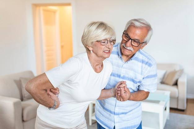 Pareja mayor en casa. hermosa anciana está teniendo dolor de espalda y su atractivo marido la apoya.