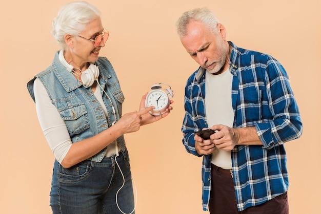 Pareja mayor chula con alarma y smartphone