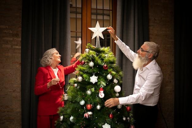 Pareja mayor, configuración, árbol de navidad