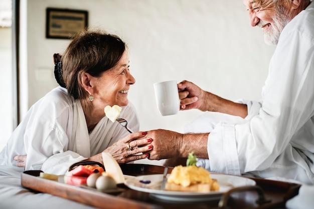 Una pareja mayor disfrutando del servicio de habitaciones.