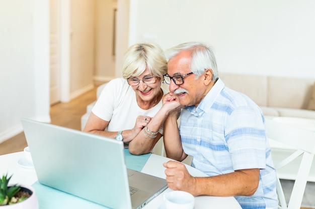 La pareja mayor está hablando en línea a través de una conexión de video en la computadora portátil