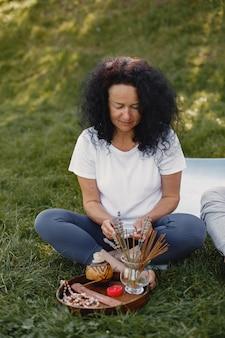 La pareja mayor está haciendo yoga al aire libre. estirarse en el parque durante el amanecer. morena con camiseta blanca.