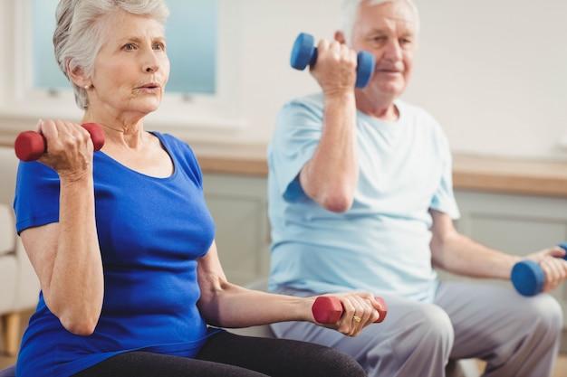 Pareja mayor, levantar pesas, mientras, sentado, en, pelota del ejercicio, en casa