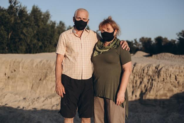 Pareja mayor con máscaras médicas para protegerse del coronavirus al aire libre en la naturaleza de verano