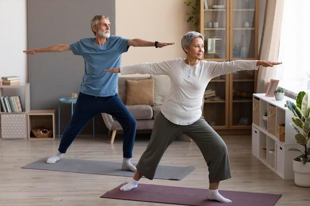 Pareja mayor, practicar, yoga, en casa