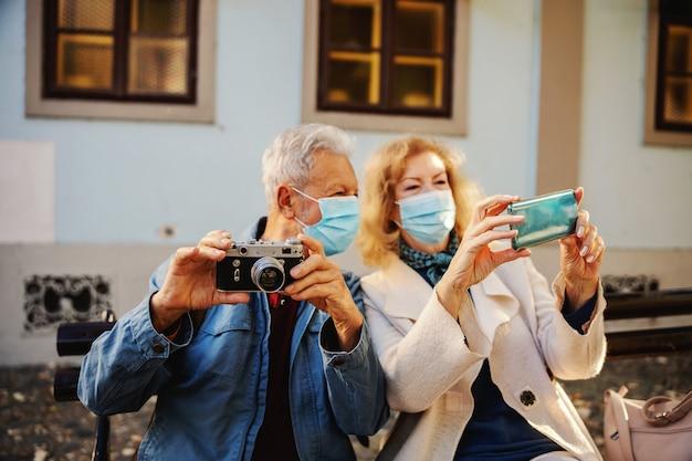Pareja mayor que usa diversas tecnologías para tomar una foto durante el virus corona.