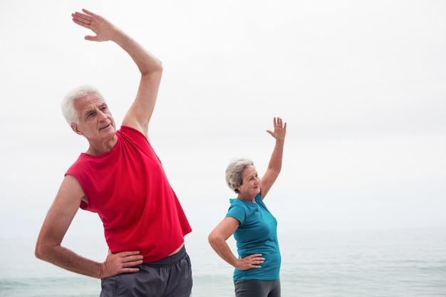 Pareja mayor, realizar, estiramiento, ejercicio