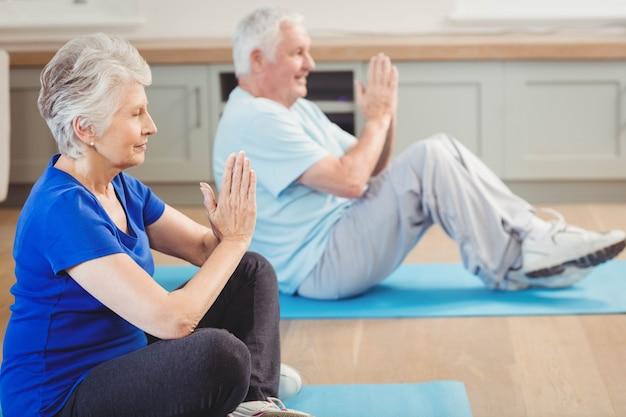 Pareja mayor, realizar, yoga, ejercicio, en casa