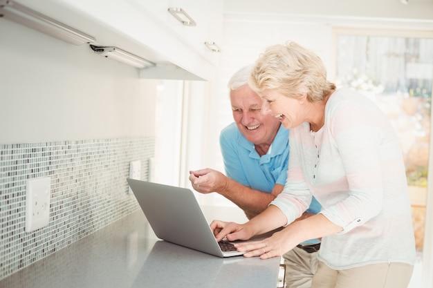 Pareja mayor, reír, mientras, usar la computadora portátil, en cocina