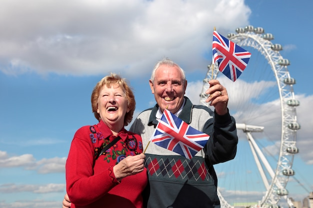 Pareja mayor sosteniendo la bandera británica en londres
