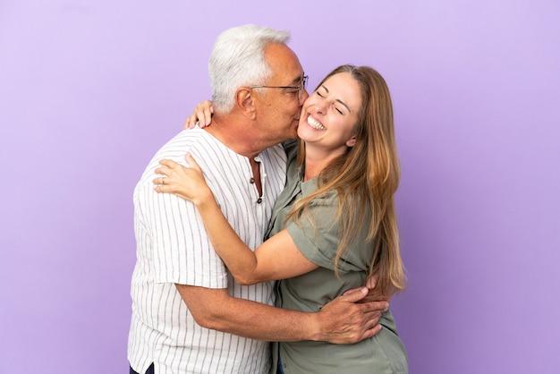 Pareja de mediana edad aislado sobre fondo púrpura besos