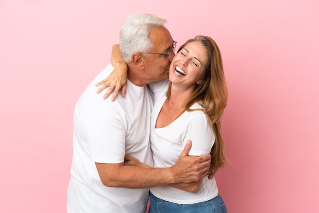 Pareja de mediana edad aislado sobre fondo rosa besos