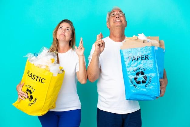 Pareja de mediana edad sosteniendo bolsas de reciclaje llenas de papel y plástico aislado sobre fondo blanco con los dedos cruzando y deseando lo mejor
