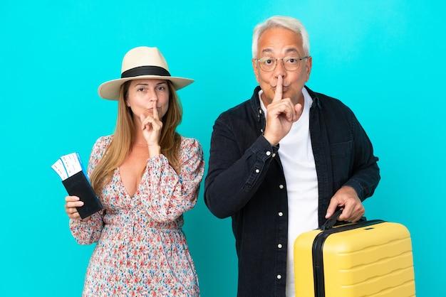 Pareja de mediana edad va a viajar y sosteniendo una maleta aislada sobre fondo azul mostrando un gesto de silencio poniendo el dedo en la boca