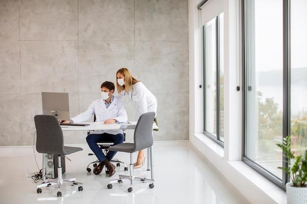 Pareja de médicos con máscaras faciales médicas protectoras hablando y usando la computadora en la oficina