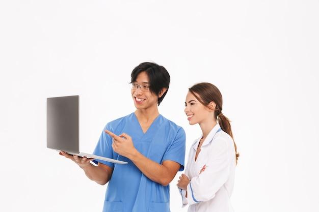 Pareja de médicos sonrientes vistiendo uniforme que se encuentran aisladas sobre la pared blanca, trabajando en equipo portátil