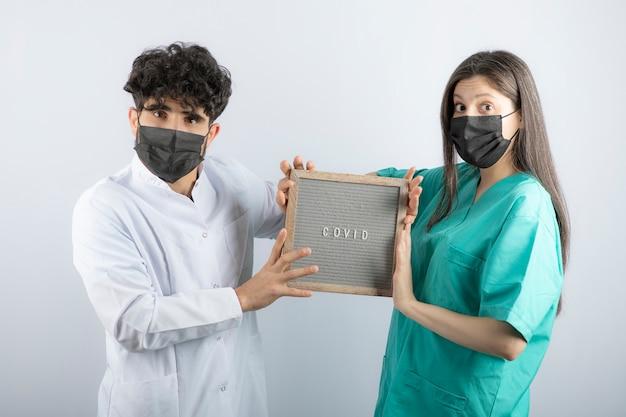 Pareja de médicos en uniformes sosteniendo un marco y mirando a cámara.