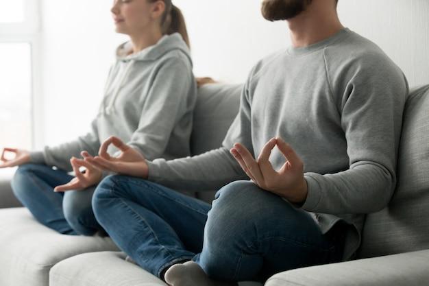Pareja meditando practicando yoga en casa sofá, se centran en las manos