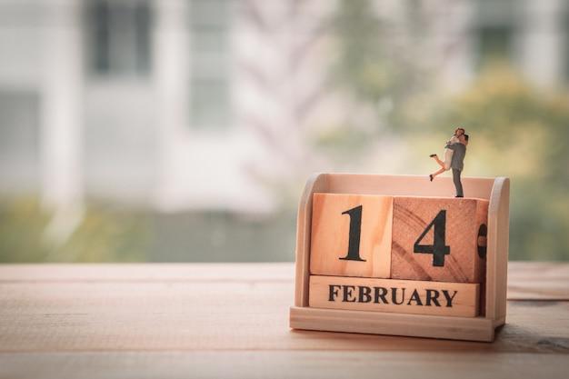 Pareja en miniatura con calendario de madera. 14 de febrero. día de san valentín.