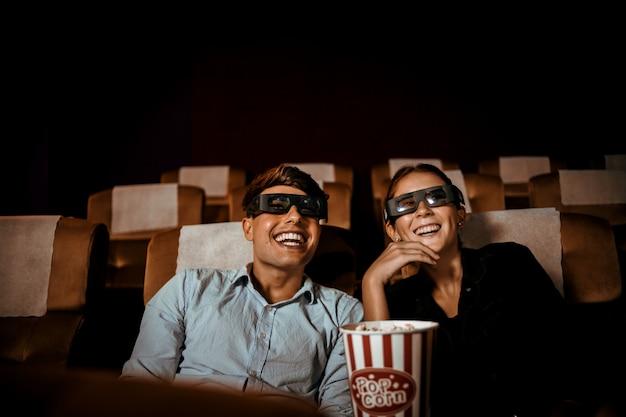 Pareja mira películas en el teatro con palomitas de maíz sonrisa y cara feliz