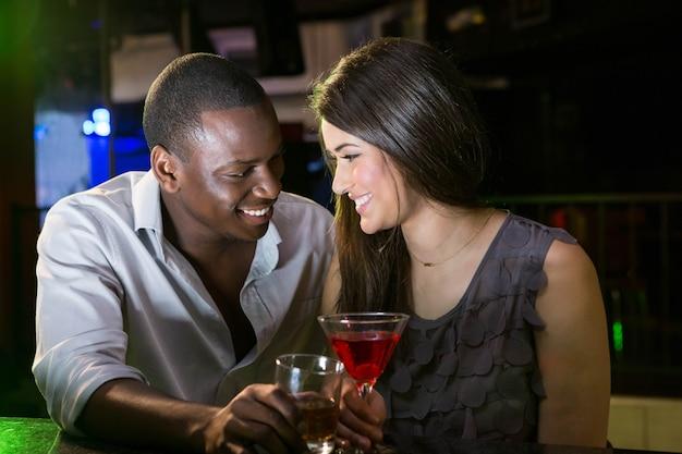 Pareja mirando el uno al otro y sonriendo mientras toma una copa en el bar