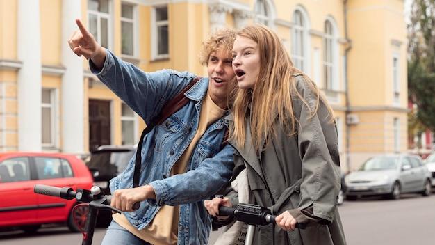 Pareja mirando algo mientras en scooters eléctricos en la ciudad