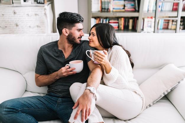 Pareja mirando el uno al otro sosteniendo la taza de café en las manos