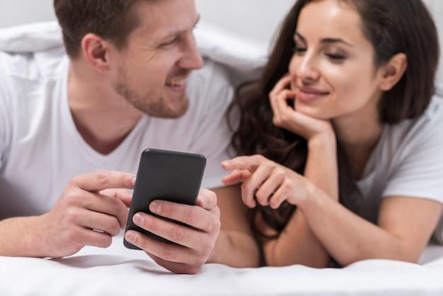 Pareja mirando juntos por teléfono