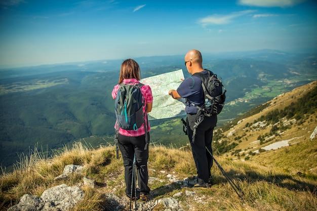 Pareja mirando un mapa en nanos plateau en eslovenia con vistas al valle de vipava
