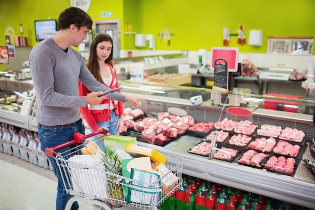 Pareja mirando el mostrador de carne