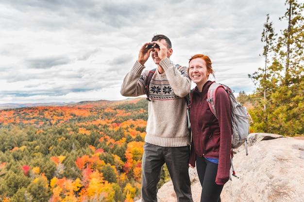 Pareja mirando el panorama con un binocular desde la cima de las rocas