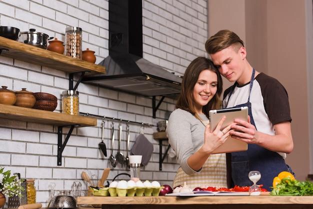 Pareja mirando la tableta mientras se abraza en la cocina