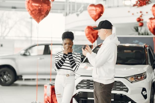 Pareja mixta. el hombre le da un coche a la chica. mujer africana con hombre caucásico.