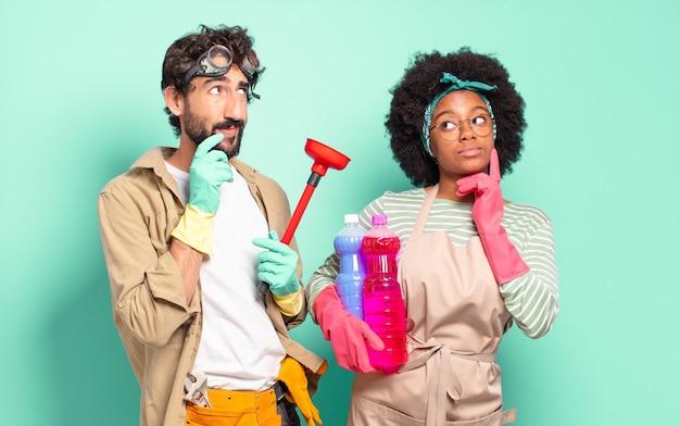 Pareja mixta sonriendo felizmente y dudando mirando hacia el lado concepto de limpieza concepto de reparaciones del hogar