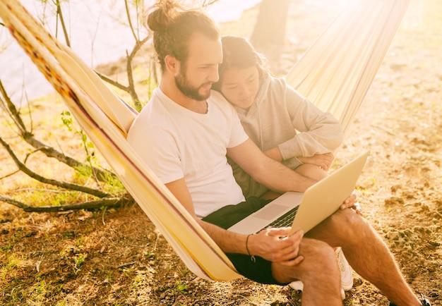 Pareja de moda descansando juntos en hamaca al aire libre