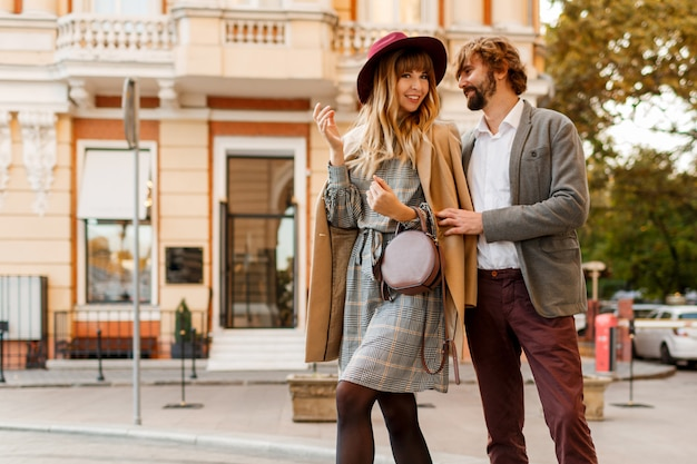 Pareja de moda feliz posando en la calle vieja en primavera soleada. mujer muy hermosa y su novio elegante guapo abrazos al aire libre.