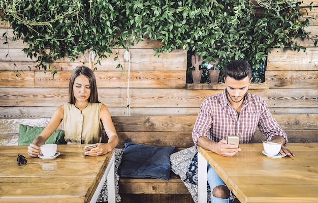 Pareja de moda en el momento de desinterés ignorándose unos a otros usando un teléfono celular móvil