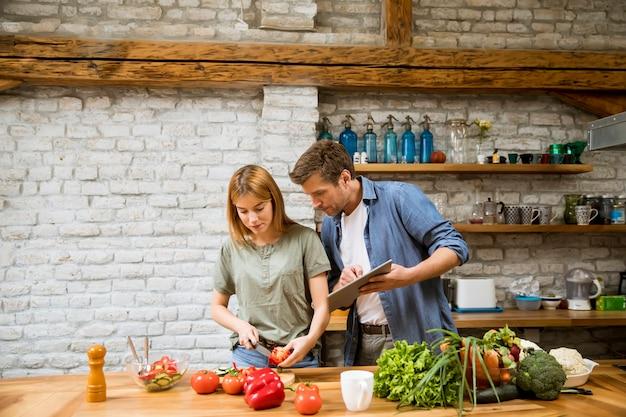 Pareja de moda pelar y cortar verduras del mercado en la cocina rústica
