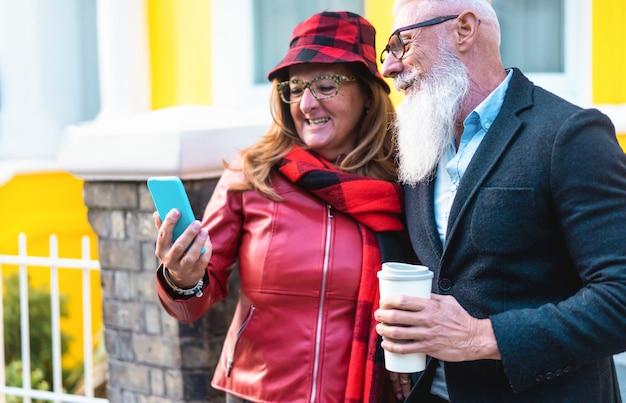Pareja de moda senior usando la aplicación de teléfono inteligente en londres - personas maduras que se divierten con el teléfono móvil - viajes, amor, influencer, tendencias tecnológicas y alegre concepto de tercera edad - centrarse en la cara del hombre