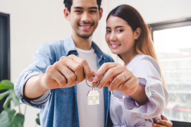 Pareja mostrando llaves apartamento después de la compra.