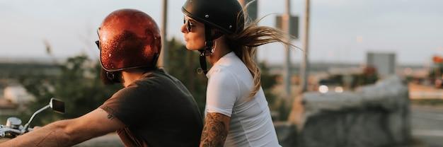 Pareja de motociclistas cabalgando por la carretera en la puesta de sol