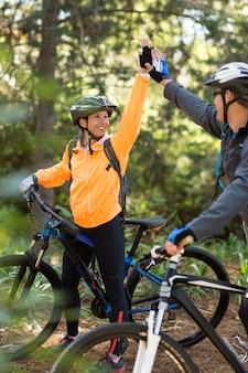 Pareja de motociclistas dando chocar los cinco al andar en bicicleta en el bosque