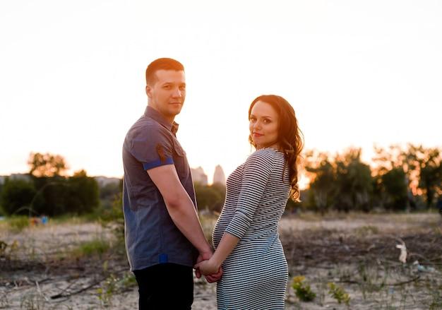 Pareja con mujer embarazada cogidos de la mano en puesta de sol