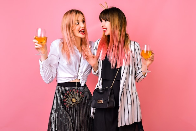 Pareja de mujer hipster de mejor amigo bastante elegante celebrando las vacaciones, elegantes trajes de noche en blanco y negro y peinado rosa de moda, tiempo de diversión juntos.