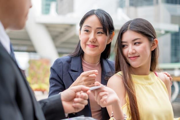 Pareja de mujer joven asiática sonriendo con tarjeta de crédito de pago con vendedor