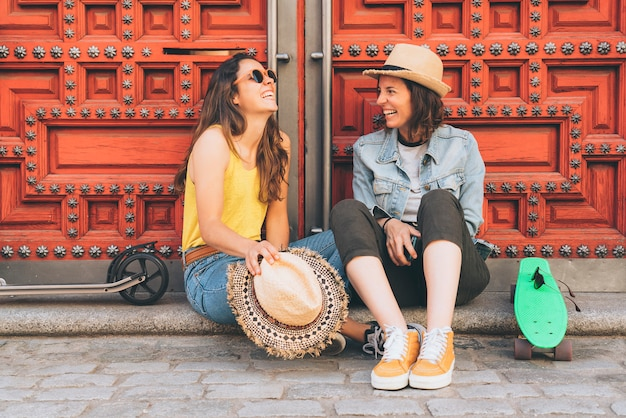 Pareja de mujeres jóvenes gay mirando y sonriendo unos a otros en una puerta roja