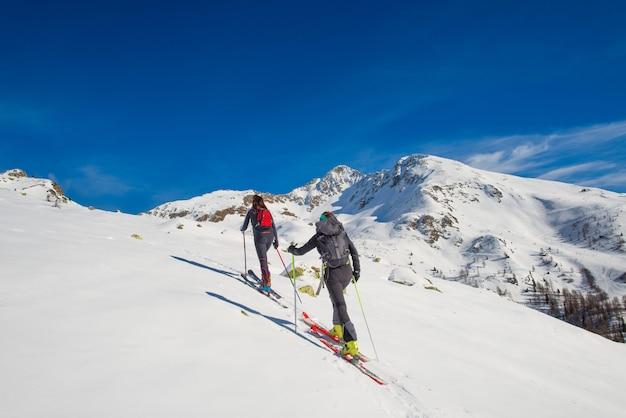 Una pareja de mujeres practica esquí de montaña