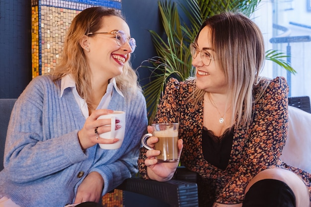 Pareja de mujeres tomando café en una terraza en vacaciones de primavera. concepto de viaje y ocio.